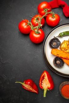 Вид сверху овощи красная скатерть помидоры специи перец тарелка жареных овощей