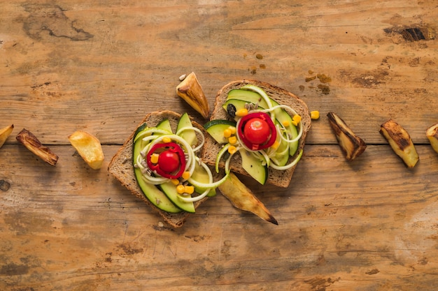 Top view of vegetables sandwich with roasted potato slice on wooden table