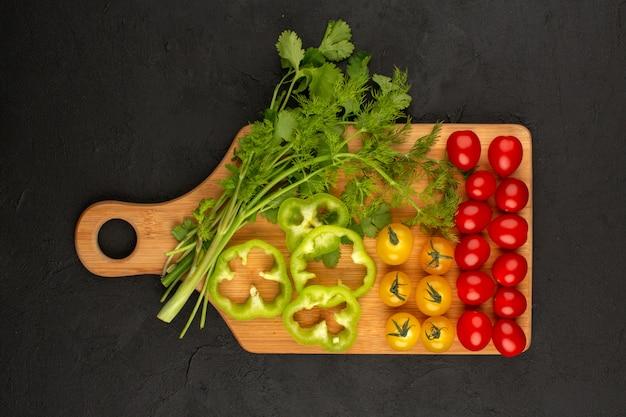 어두운 배경에 녹색 피망 노란색 빨간 토마토와 같은 상위 뷰 야채 슬라이스 및 전체