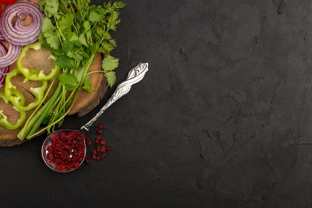 Вид сверху овощи нарезанный свежий целый лук зеленый перец и зелень на темном фоне