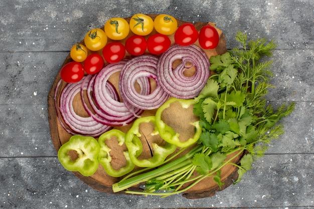 Vista dall'alto verdure tagliate intere come cipolle peperoni verdi e pomodori su sfondo grigio