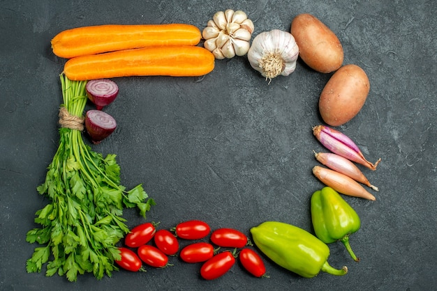 Top view of vegetables in square and with free place for your text in the center on dark grey background