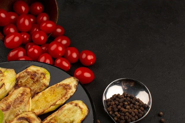 Top view vegetables such as cooked eggplants and red cherry tomatoes on the dark background