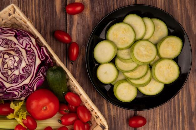 Vista dall'alto di verdure come pomodori sedano cavolo cappuccio viola e zucchine su un secchio con zucchine tritate su un piatto su una parete in legno