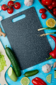 Top view of vegetables with cutting board on blue surface