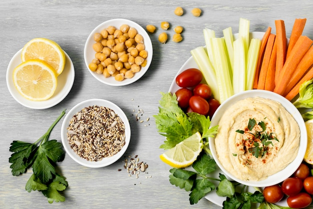 Top view of vegetables with hummus and lemons