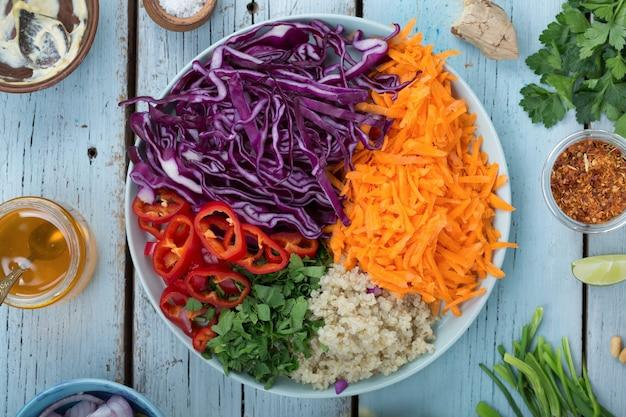 Вид сверху вегетарианский салат из красной капусты и киноа в миске на синем деревянном фоне