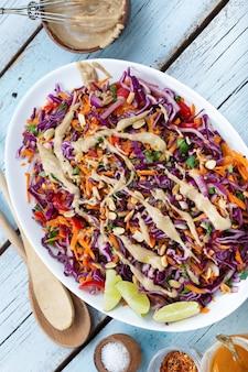 Вид сверху вегетарианский салат из красной капусты и киноа в тарелке на синем деревянном фоне
