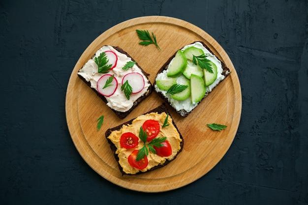 Вид сверху вегетарианские бутерброды из ржаного хлеба с творогом, хумусом, авокадо, редисом и томатом. деревянная доска на черной поверхности