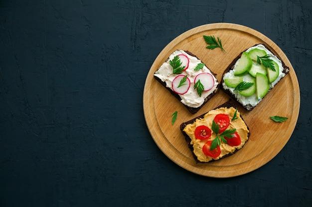 Вид сверху вегетарианские тосты из ржаного хлеба с творогом, хумусом, авокадо, редисом и помидорами на деревянной доске, черный фон, место для текста