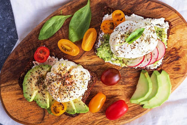 Top view vegetarian toast with poached egg, cottage cheese, avocado and vegetables on wooden board, light snack, healthy breakfast concept