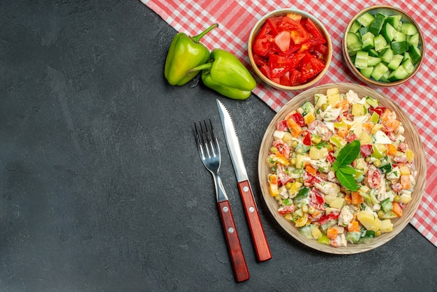 Top view of veggie salad in bowl with red napkin under it and cutleries with vegetables on side and place for text on dark grey background