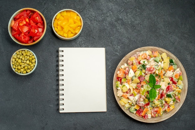 Top view of veggie salad with bowls of vegetables and notepad on side on dark grey background