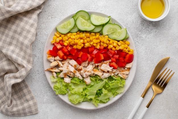 Вид сверху вегетарианский салат с курицей и столовыми приборами