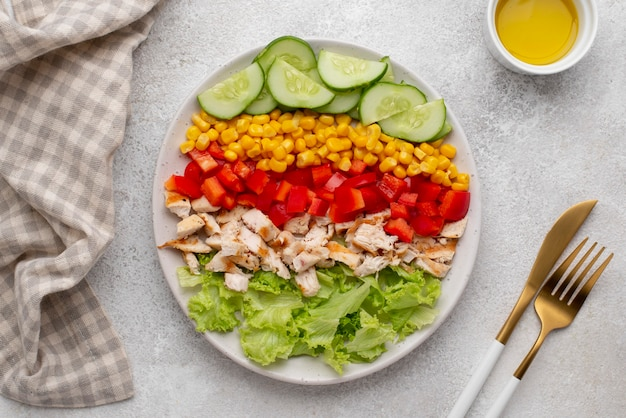 Top view veggie salad with chicken and cutlery