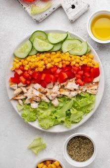 닭고기, 허브, 기름을 곁들인 상위 뷰 야채 샐러드