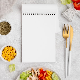 Top view veggie salad with chicken and herbs with blank notepad