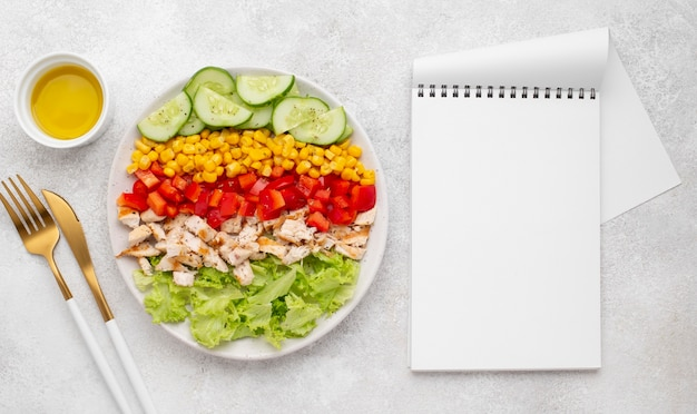 Top view veggie salad with chicken and oil with blank notenook