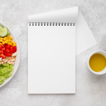 Top view veggie salad with chicken and oil with blank notepad