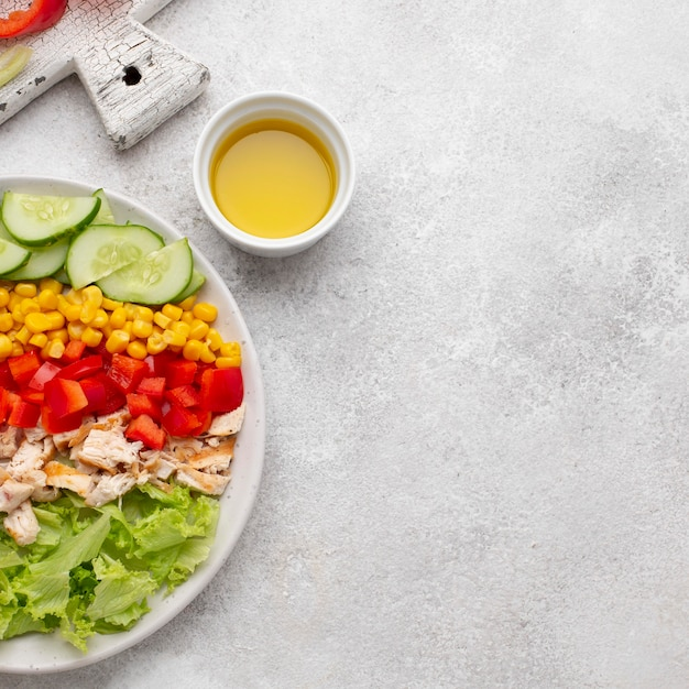Top view veggie salad with chicken and oil with copy-space