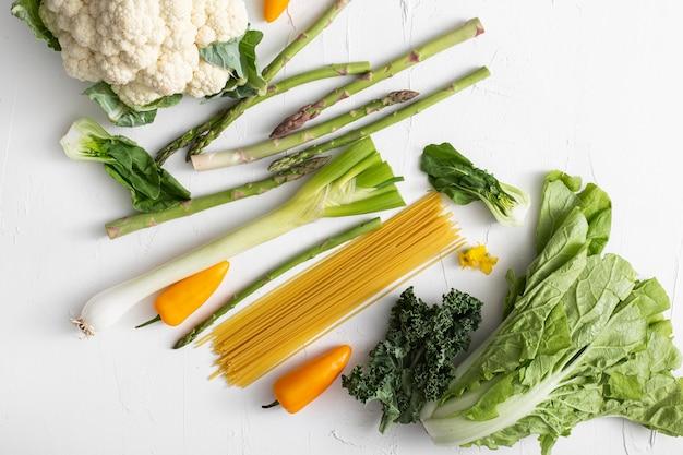 Вид сверху на овощи и сырые спагетти