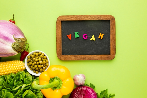 Top view veggies on green background with vegan lettering
