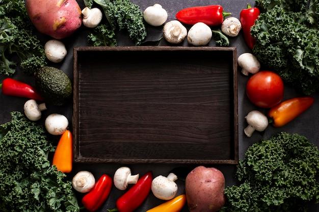 Le verdure con vista dall'alto si mescolano con un vassoio di legno vuoto