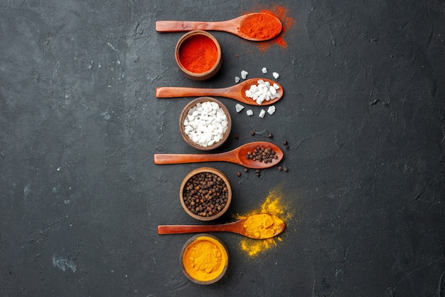 Top view vertical row bowls with turmeric black pepper sae salt red pepper powder wooden spoons on black table free space