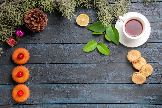 Top view vertical row cherry cupcakes cone fir-tree leaves christmas toys slice of lemon a cup of tea and biscuits on dark wooden table with copy space