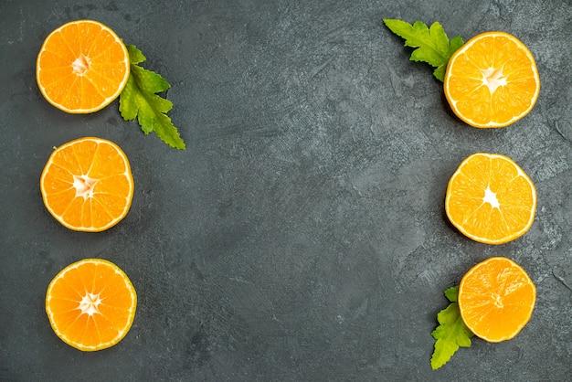Top view vertical row cut oranges on dark background free space