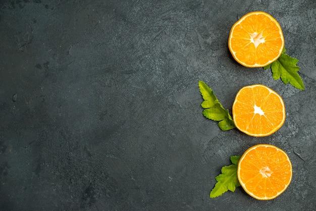 Вид сверху вертикальный ряд нарезанных апельсинов на темном фоне свободного пространства