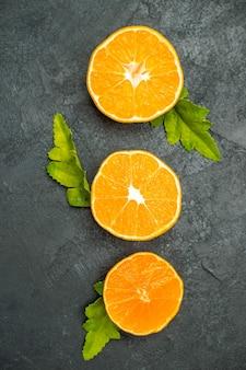 상위 뷰 수직 행은 어두운 표면에 오렌지를 잘라냅니다.