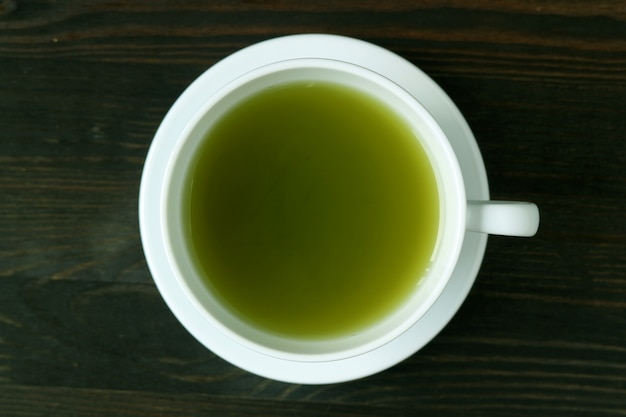 Top view of vibrant green color hot matcha green tea on dark brown wooden table