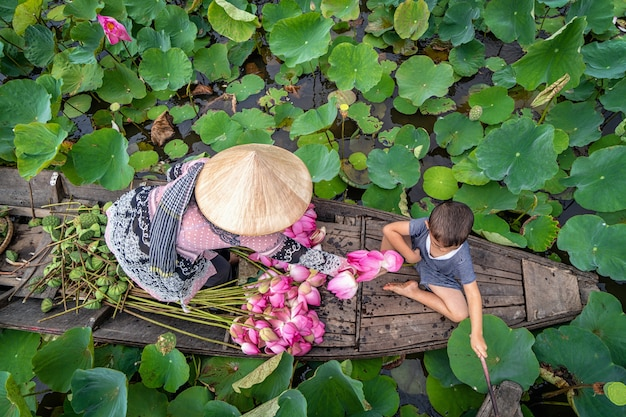 Top view of vietnamese boy playing with mom over the traditional wooden boat