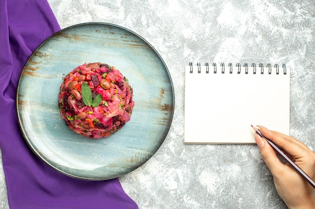 Top view vinaigrette beet potato salad on round plate purple shawl notepad pencil in female hand on light table