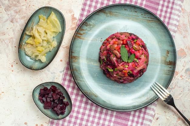 上面図のビネグレットサラダと白と紫の市松模様のテーブルクロスボウルの楕円形プレートのフォークとライトグレーのテーブルの他のもの