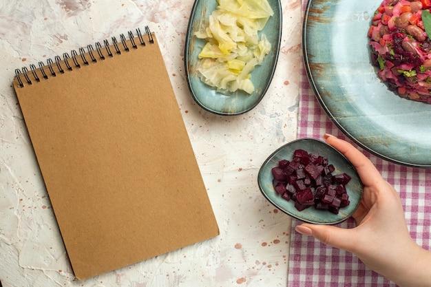 白と紫の市松模様のテーブルクロスにシアンの楕円形プレートにビネグレットサラダを上から見たライトグレーのテーブルに女性の手のメモ帳にビートボウルをカット
