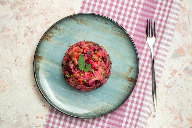 楕円形のプレートにトップビューのビネグレットサラダ、ライトグレーのテーブルに白と紫の市松模様のテーブルクロスにフォーク