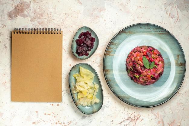 楕円形のプレートカットビートのトップビュービネグレットサラダとライトグレーのテーブルのボウルノートブックの他のもの