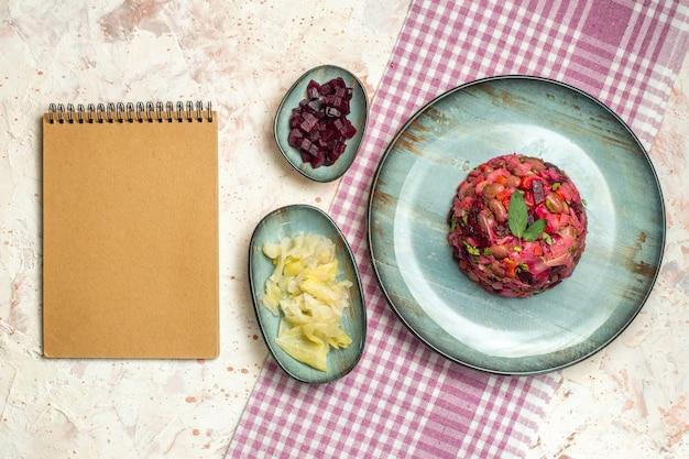 楕円形のプレートカットビートのトップビュービネグレットサラダとライトグレーのテーブルの紫と白の市松模様のテーブルクロスノートのボウルに他のもの