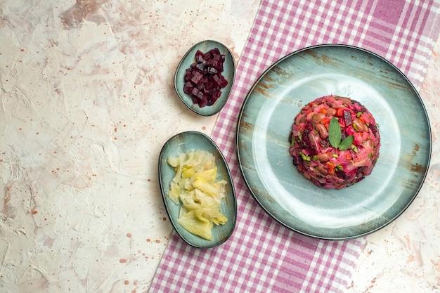 楕円形のプレートカットビートのトップビュービネグレットサラダと他のものをボウルに入れて、空きスペースのあるライトグレーのテーブルに紫の白い市松模様のテーブルクロスをかけます