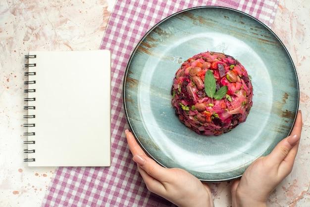 ライトグレーのテーブルの上の女性の手紫白い市松模様のテーブルクロスノートの楕円形のプレート上の上面図ビネグレットサラダ