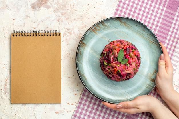 白と紫の市松模様のテーブルクロスの上の女性の手の楕円形のプレート上の上面図ビネグレットサラダライトグレーのテーブルの上のノート