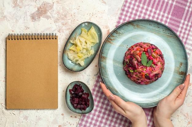 白と紫の市松模様のテーブルクロスボウルに女性の手で楕円形のプレートにビネグレットサラダの上面図ライトグレーのテーブルにいくつかのスタッフのノートブック