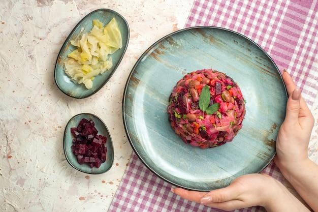 白と紫の市松模様のテーブルクロスボウルに女性の手で楕円形のプレートにビネグレットサラダを上から見たライトグレーのテーブルにいくつかのものを