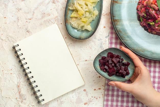 ライトグレーのテーブルの上の女性の手のノートのカットビートと白と紫の市松模様のテーブルクロスボウルの楕円形のプレート上の上面図ビネグレットサラダ