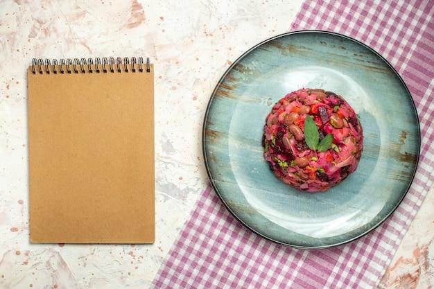 楕円形のプレートに上面図のビネグレットサラダライトグレーのテーブルに紫と白の市松模様のテーブルクロスのメモ帳