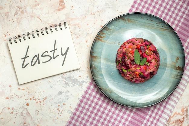 ライトグレーのテーブルのノートに書かれた楕円形のプレート紫白市松模様のテーブルクロスのトップビュービネグレットサラダ