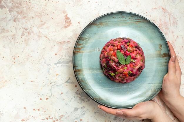 Insalata di vinaigrette vista dall'alto su piatto ovale in mano femminile su spazio libero tavolo grigio chiaro
