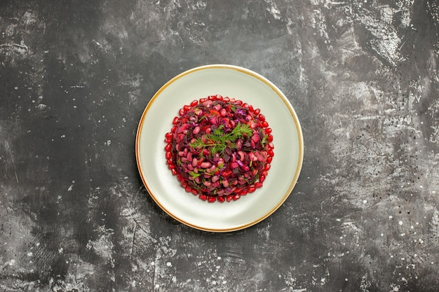 灰色の表面にザクロと豆のトップビュービネグレットサラダ